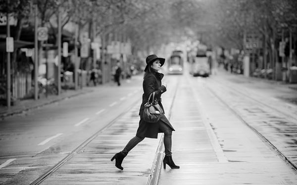 lady in trench coat crossing intersection on a cold winters day in melbourne