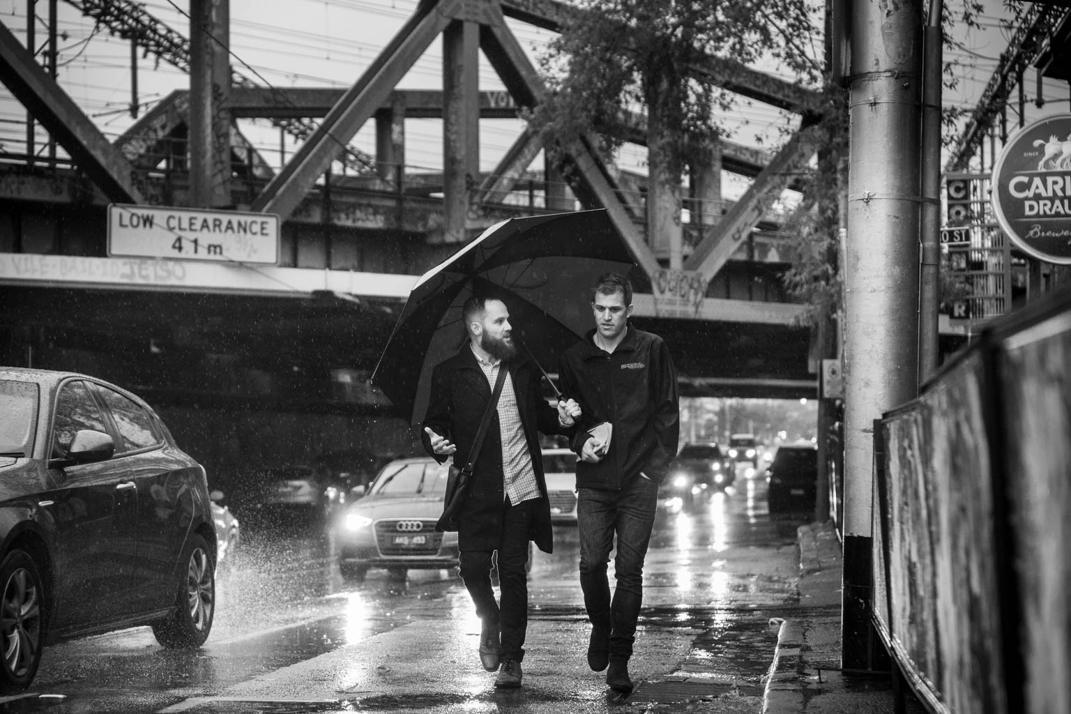 two men with umbrella walking on a cold rainy day in richmond