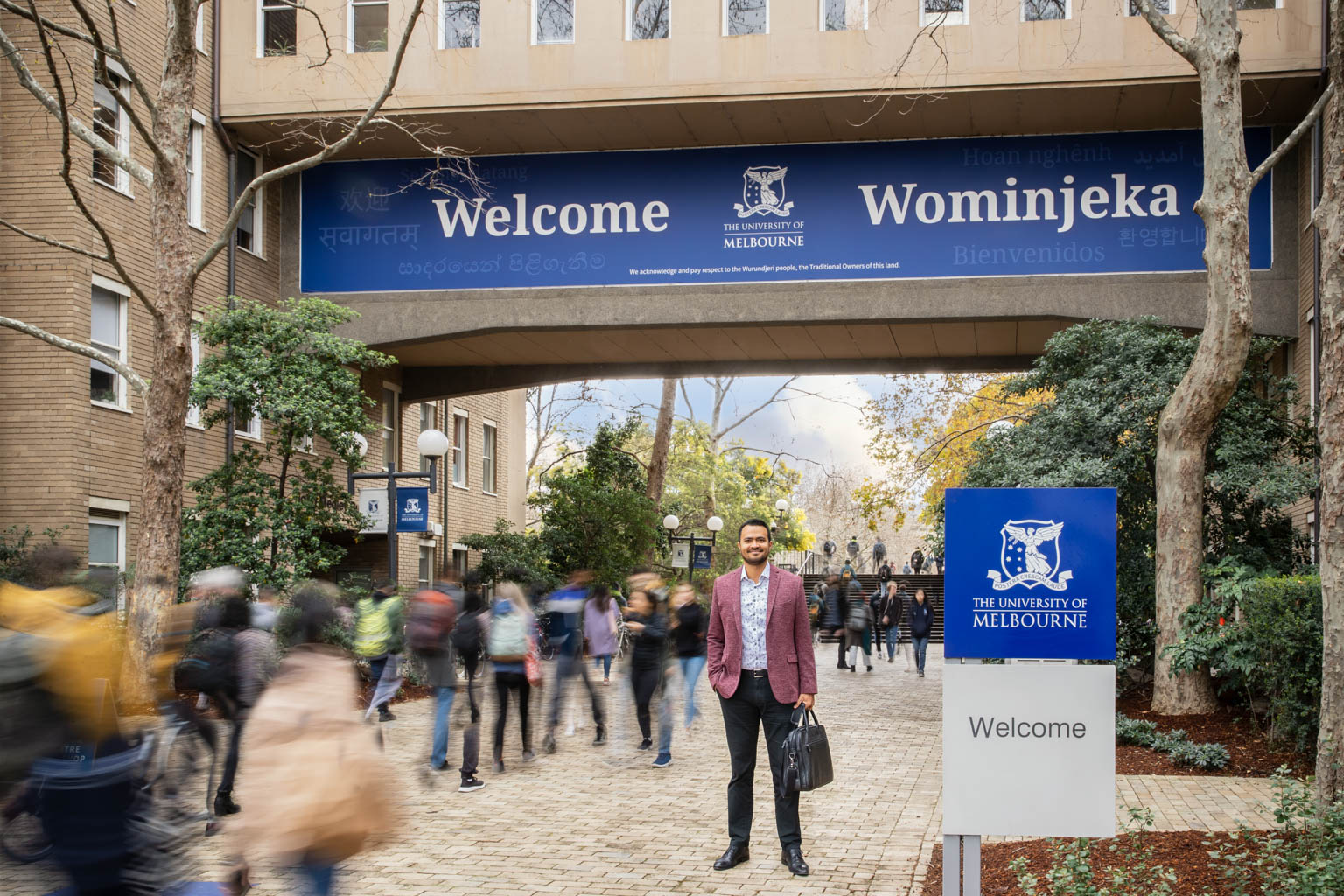 commercial photography of man standing under arch way at melbourne university entrance