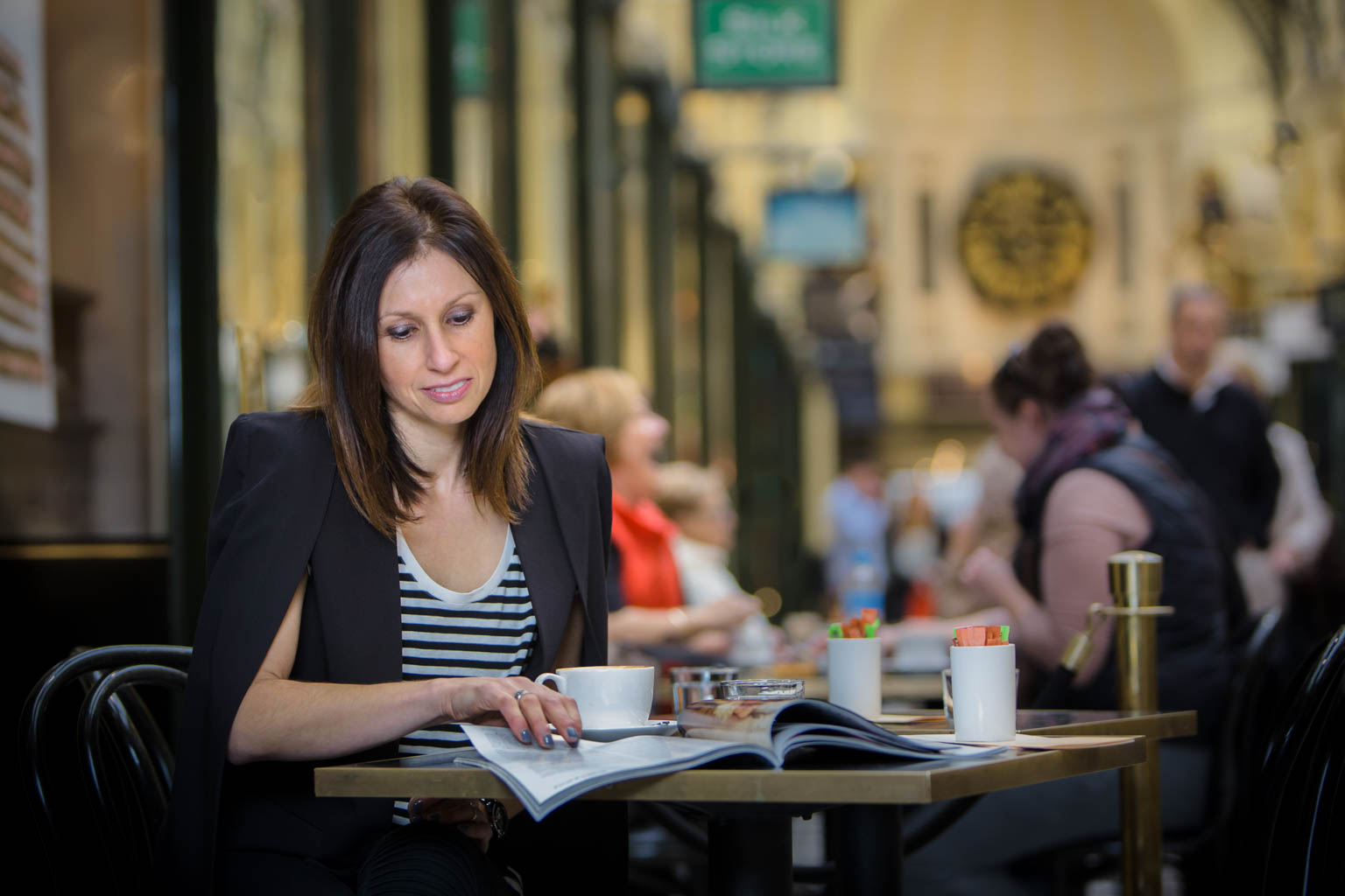 commercial photography of lady having a cup of coffee and reading a magazine in melbourne arcade