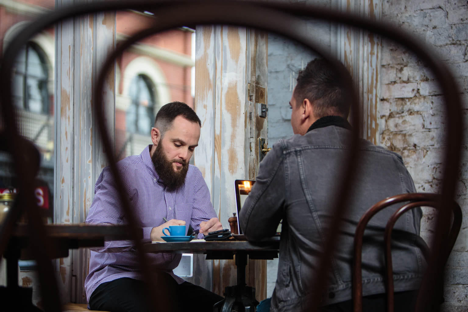 commercial photography of two men having business meeting with coffee and laptop in melbourne