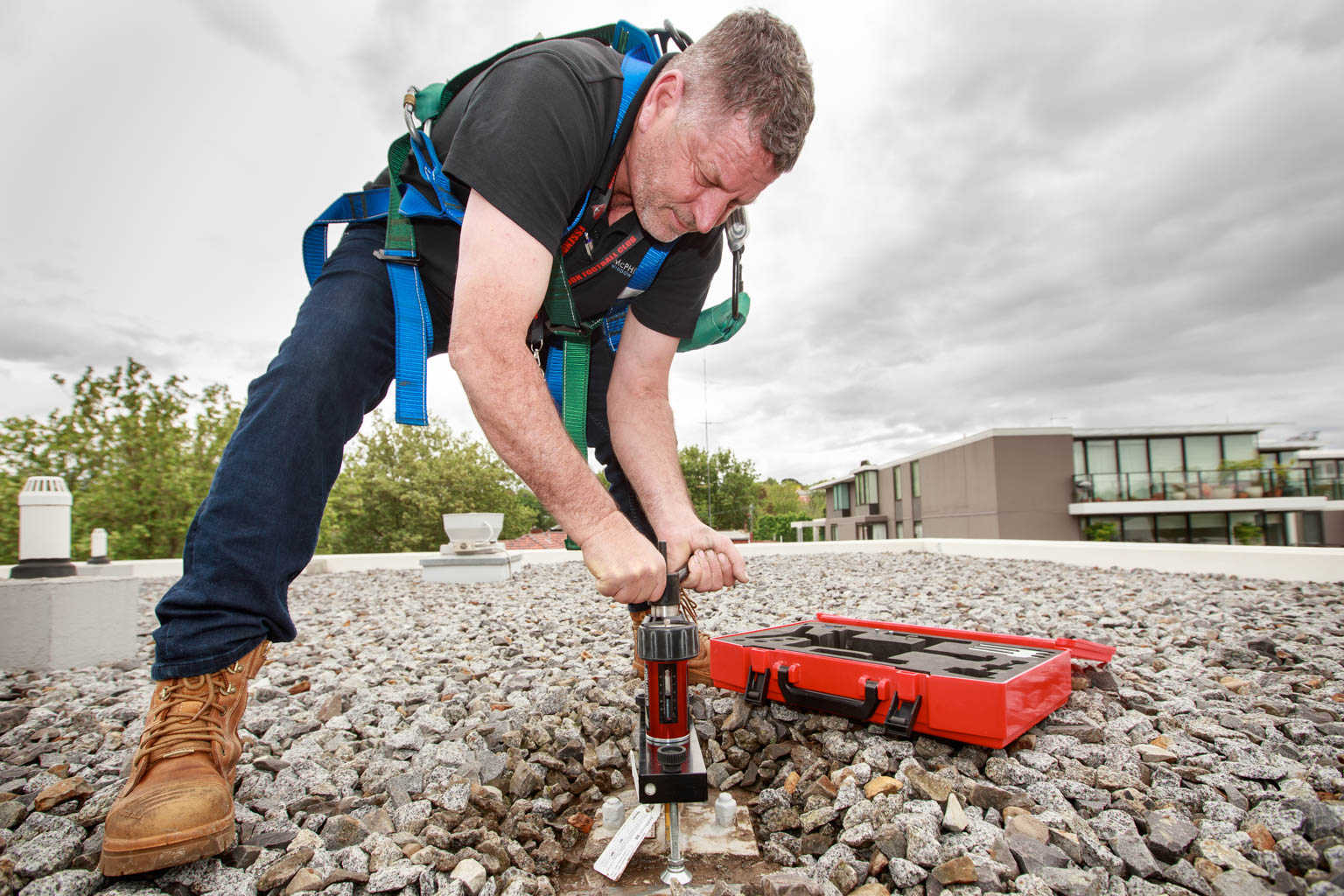 commercial photography of man on building roof pressure testing safety point