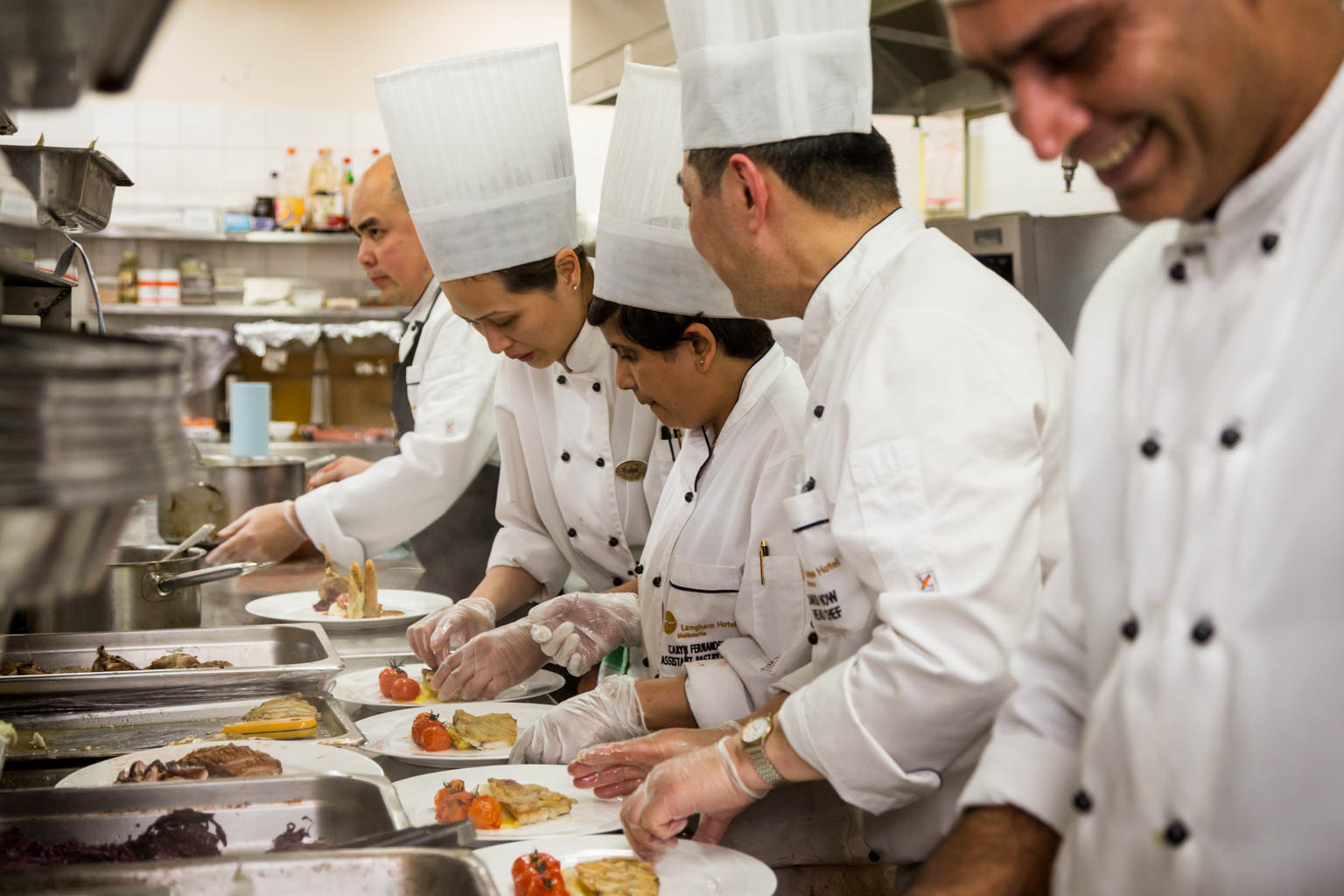chefs in commercial hotel kitchen plating food