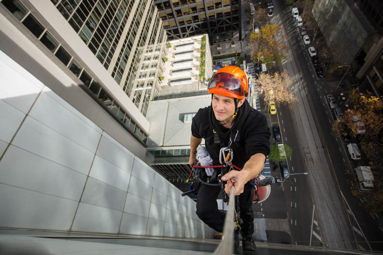 melbourne commercial window washer hanging over edge of building