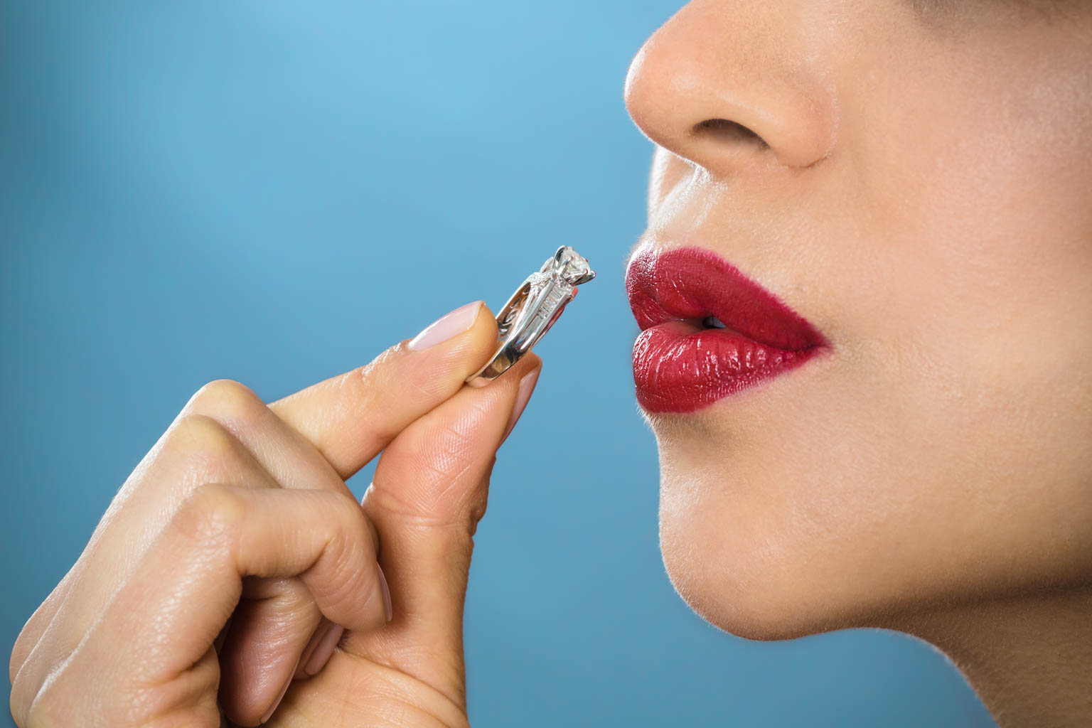 girl with red lips kissing a diamond engagement ring