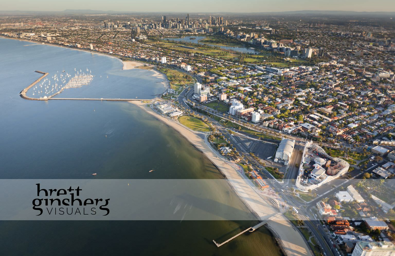 aerial drone photograph of luna park, st kilda pier and marina with city skyline melbourne