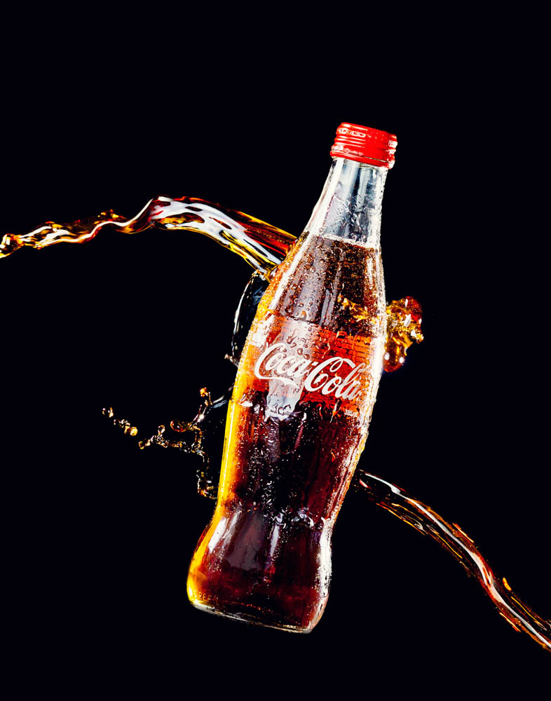 product photography of coca cola bottle with splashing cola